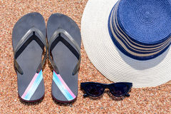 Sunglasses, Slip slops and sunhat on a tropical beach. Overhead view of a Sunglasses, pair of casual slip slops and sunhat on a tropical beach conceptual of a Stock Photography