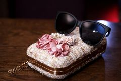 Sunglasses on a small women`s stylish handbag. stock photos