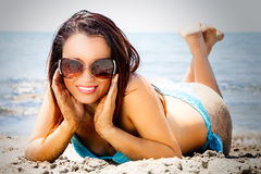 Sunglasses, smiling fashion woman on the sand. Holiday. A beautiful woman with a beautiful smile is lying face down on the sand to the sea. She wears a large Stock Photos