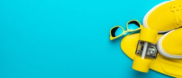 Sunglasses, sneakers, mini cruiser board on blue background with copy space. Top view panoramic image of yellow modern teenage accessories. Flat lay photo of stock photo