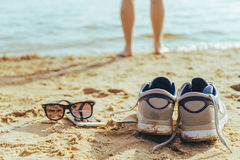 Sunglasses with snickers on the beach, man stands on background Royalty Free Stock Photography