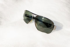Sunglasses in the snow. Sunglasses on the snow. Sunny day. White snow Royalty Free Stock Photo