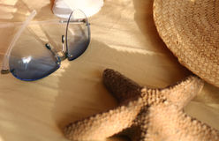 Sunglasses and starfish. Still-life of sunglasses,starfish,straw-hat and shell in the sunlight stock photography