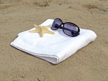 Sunglasses and starfish on white towel Royalty Free Stock Image
