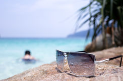 Sunglasses on the stone with blur people swiming in see. View in sunnyday Royalty Free Stock Photo