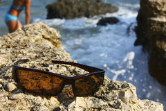 Sunglasses on the stone coast Stock Images
