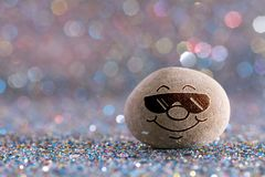 The sunglasses stone emoji. Emotions on color glitter boke background stock photography