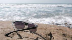 Sunglasses on the stone by the sea. Sunglasses on the stone by the sea stock video