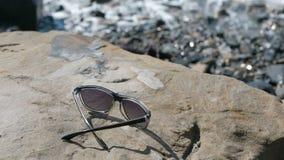 Sunglasses on the stone by the sea. Sunglasses on the stone by the sea stock footage