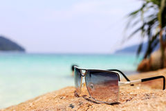 Sunglasses on the stone with see Royalty Free Stock Photo