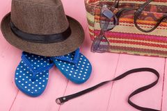 Sunglasses, straw beach bag, sun hat, belt and flip flops on pink wooden table. Summer accessories - sunglasses, straw beach bag, sun hat, belt and flip flops on Stock Photos