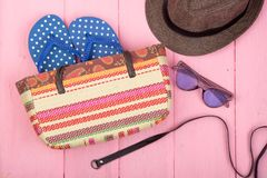 Sunglasses, straw beach bag, sun hat, belt and flip flops on pink wooden table. Summer accessories - sunglasses, straw beach bag, sun hat, belt and flip flops on Stock Images