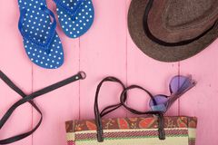Sunglasses, straw beach bag, sun hat, belt and flip flops on pink wooden table. Summer accessories - sunglasses, straw beach bag, sun hat, belt and flip flops on Royalty Free Stock Photos