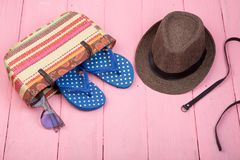 Sunglasses, straw beach bag, sun hat, belt and flip flops on pink wooden table. Summer accessories - sunglasses, straw beach bag, sun hat, belt and flip flops on Royalty Free Stock Photography
