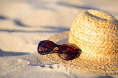 Sunglasses and straw hat closeup on the sand at the beach Stock Photography