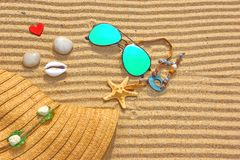 Sunglasses, Straw Hat and  different objects on the beach sand. Sunglasses, Fashion Straw Hat, shells, stones and wooden heart on the beach sand. Marine Summer Stock Image