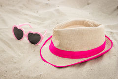 Sunglasses and straw hat on sand at beach, sun protection, summer time Royalty Free Stock Photo