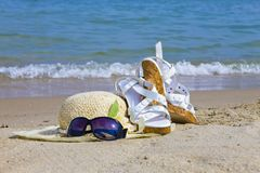 Sunglasses, Straw hat and sandal lay on sand Stock Photos