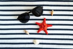 Summer, some sea stuff on white and stripped. Sunglasses, straw hat, seastar, stripped towel on white royalty free stock photo