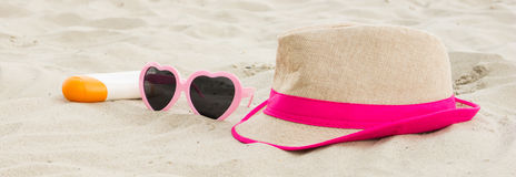 Sunglasses, straw hat and sun lotion on sand at beach, sun protection, summer time Royalty Free Stock Photo