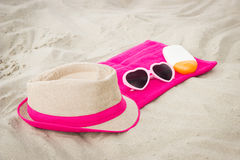 Sunglasses, straw hat and sun lotion on sand at beach, sun protection, summer time Royalty Free Stock Images