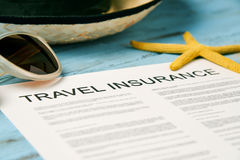 Sunglasses, straw hat and travel insurance policy Stock Photos