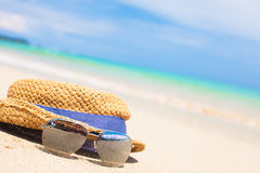 Sunglasses and straw hat on tropical beach Royalty Free Stock Photography