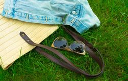 Sunglasses,  summer bag and denim jacket on green grass. The concept of summer walks and outdoor recreation. Sunglasses, women`s summer bag and denim jacket on royalty free stock image