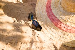 sunglasses and a summer hat on the beach sand. Relaxing vacation concept image royalty free stock images