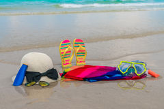 .Sunglasses, sun cream and hat  on white  sand beach Royalty Free Stock Image