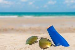 .Sunglasses and sun cream on white  sand beach. Sunglasses and sun cream on white  sand beach Stock Image