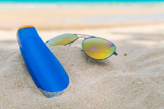 .Sunglasses and sun cream on white  sand beach Royalty Free Stock Photo