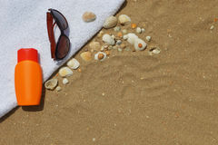 Sunglasses and sunblock on beachtowel Stock Images