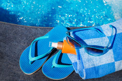 Sunglasses with sunscreen cream, blue slippers and towel on bord Stock Photos