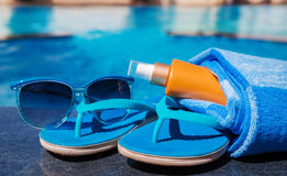 Sunglasses with sunscreen cream, blue slippers and towel on bord Royalty Free Stock Photo