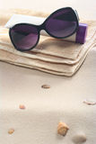 Sunglasses, Sunscreen and Towel on Sand Stock Photography