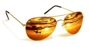 Sunglasses Sunset. Gold rimmed mirrored sunglasses reflecting sunset and airplane on a white background Stock Photo