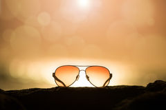 Sunglasses at Sunset and Defocused Horizon Stock Photo