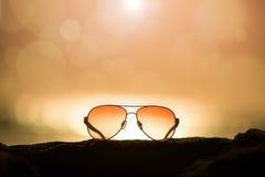 Sunglasses at Sunset and Defocused Horizon Stock Photo