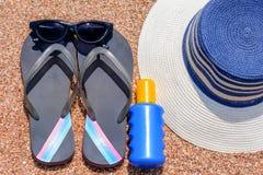 Sunglasses, suntan lotion, Slip slops and sunhat on a tropical beach Stock Photography