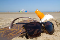 Sunglasses and suntan oil Stock Photos