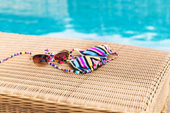 Sunglasses with swimsuit on a sun lounger near swimming pool Stock Image