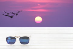 Sunglasses on table with blurred birds flying among sunrise scap Royalty Free Stock Photos