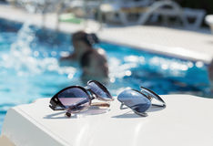 Sunglasses on a table near the swimming pool Royalty Free Stock Images