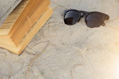 Sunglasses with text book on sand beach. For relax on holiday Stock Photography