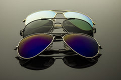 Sunglasses three pairs. Sunglasses different in shape and color pairs on a dark background with reflection Stock Images