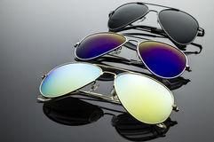 Sunglasses three pairs. Sunglasses different in shape and color pairs on a dark background with reflection Royalty Free Stock Photography