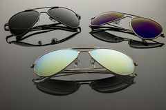 Sunglasses three pairs. Sunglasses different in shape and color pairs on a dark background with reflection Royalty Free Stock Image