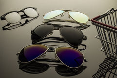 Sunglasses three pairs. Sunglasses different in shape and color pairs on a dark background with reflection Royalty Free Stock Photos