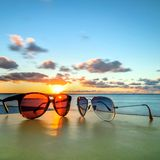 Sunglasses on tropical beach table at sunset Stock Photos